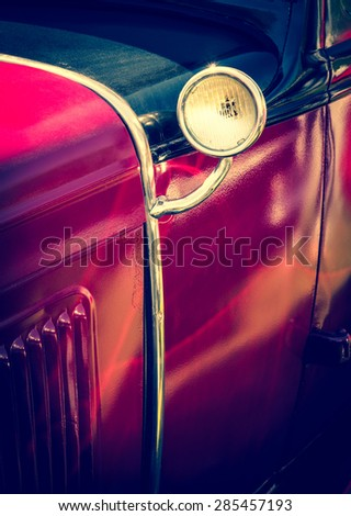 Old red car with vintage lamp - detail of retro car. Vintage auto headlight - part of antique automobile. - stock photo