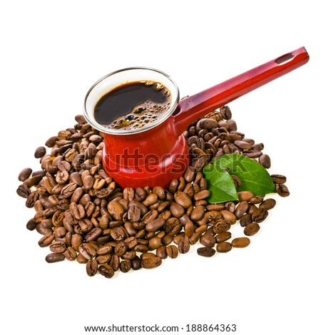 Old red coffee maker and roasted coffee beans scattered decorated with green leaves, isolated on white background - stock photo