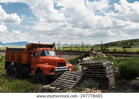 Old red country truck near of train tracks. - stock photo