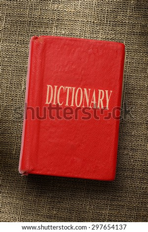 Old red dictionary on the sack background - stock photo