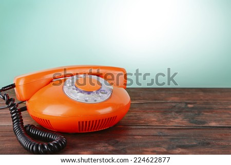 Old red disk phone on wooden table on blue background - stock photo
