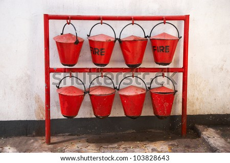 old red fire buckets hanging on support - stock photo