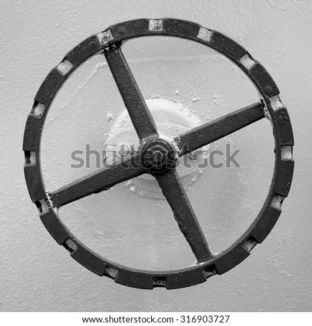 old red hand wheel on the wall of big oil tank - stock photo