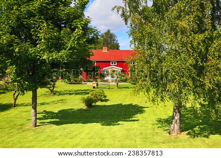 old red house in a lush green garden, summer time in Sweden - stock photo