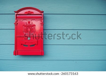 Old red mailbox on wooden walls painted blue, thailand. - stock photo