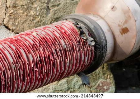 Old red pipe with black tape connection on grate. - stock photo