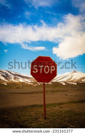 old red  road stop sign is on the road - stock photo