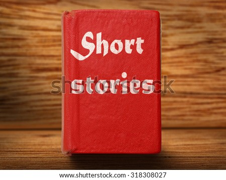 Old red short stories book on wooden background closeup - stock photo