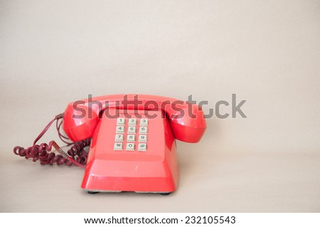 old red telephone on paper background - stock photo