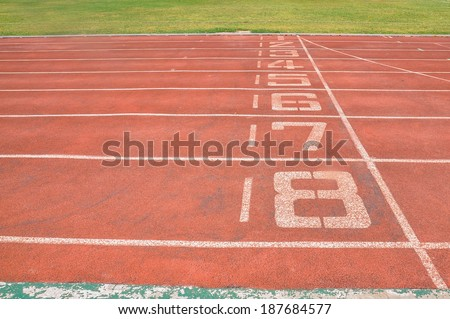 Old red treadmill at the stadium with the numbering from one to eight - stock photo