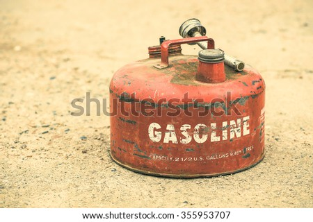 Old red vintage gasoline can on concrete background (Shallow DOF) - stock photo