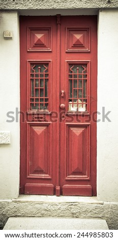 Old red wooden door with window and grid. Toned. - stock photo
