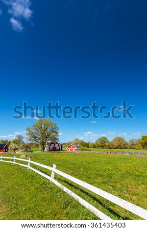 Old red wooden farm buildings with white fence in Smaland, Sweden - stock photo