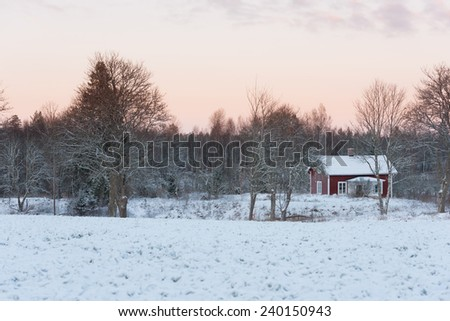 Old red wooden house in the swedish countryside, Hoegsby district, in winter. - stock photo