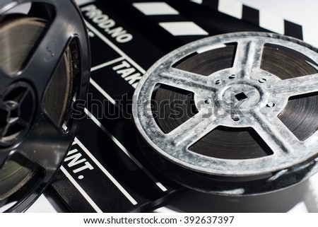 Old reel of film and cinema clap lying on a light table.  - stock photo