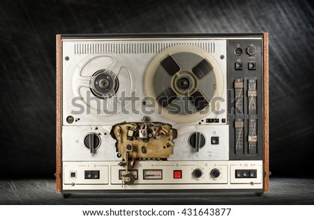 Old reel tape recorder on steel background - stock photo