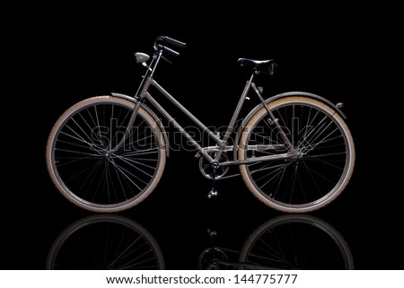Old refurbished retro bike isolated on black background with reflection side view - stock photo