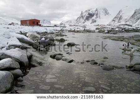 old research station and a colony of penguins around the mountains in the background of the Antarctic Peninsula - stock photo