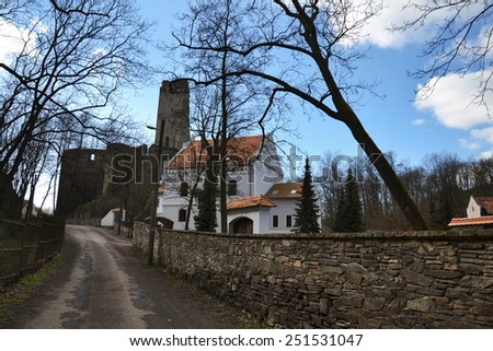 Old restored house with ruins of the Okor castle in backround,  Czech Republic - stock photo