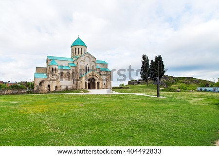 old restored temple of David the Builder Kutaisi 2014. before the temple there is a stone fence and high conifer - stock photo