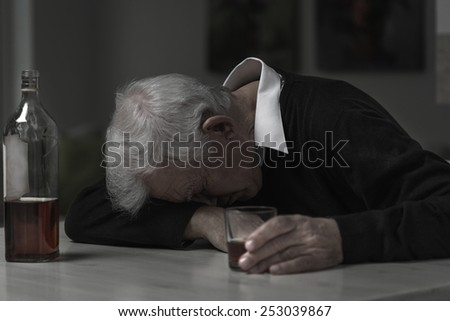 Old retired man alcoholic sleeping on the table - stock photo