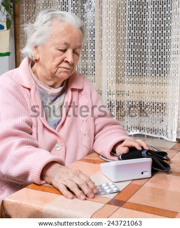 Old  retired woman taking blood pressure at home - stock photo