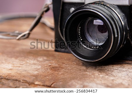 Old retro camera on rustic wooden planks background - stock photo
