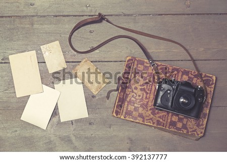 old retro camera on vintage photo album and blank pictures - stock photo