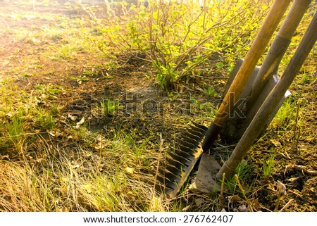 Old retro garden tools (cultivator, shovel, rake) over brown soil close up, horizontal.  Agriculture, gardening, soil cultivation, village life concept. - stock photo
