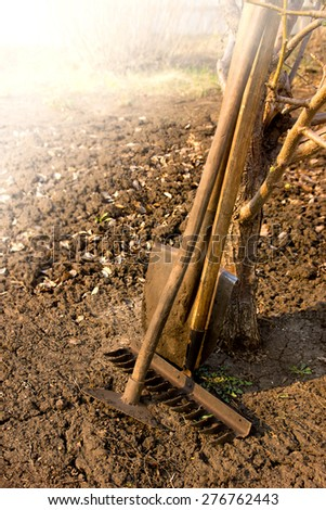 Old retro garden tools (cultivator, shovel, rake) over brown soil (ploughed land) close up, vertical.  Agriculture, gardening, soil cultivation, village life concept. - stock photo