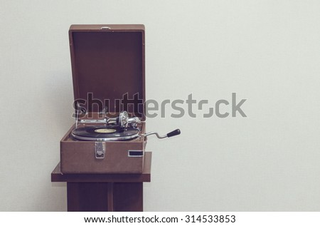 Old retro portable gramophone isolated, vintage style toned, with empty space - stock photo