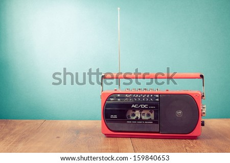 Old retro red radio cassette recorder on table in front mint green background - stock photo