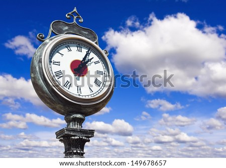 old retro street clock on a sky background - stock photo