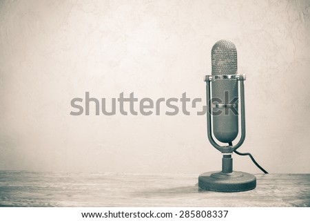Old retro studio microphone from 50s on table. Vintage style sepia photo - stock photo