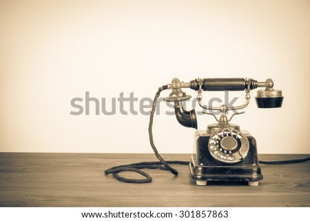 Old retro telephone on table. Vintage style sepia photo - stock photo