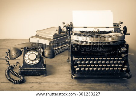 Old retro telephone, typewriter, books on table. Vintage style sepia photo - stock photo