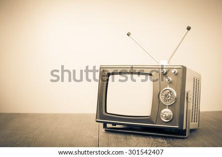 Old retro TV on table. Vintage style sepia photo - stock photo