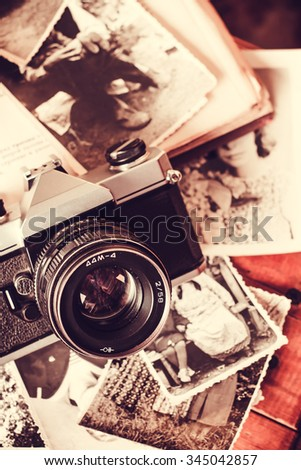 Old retro vintage camera and books photography. Antique lens equipment. Black object film photo. Classic creative background. Table image. Obsolete nostalgia style.  - stock photo
