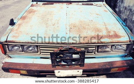 Old retro vintage car or automobile front side with front lights or headlights and radiator grill with vintage retro style color - stock photo