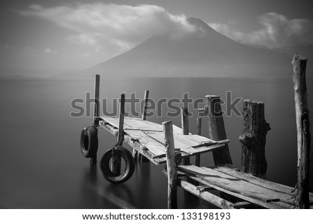 Old rickety wooden pier juts out into lake Atitlan (Guatemala) with volcano in background.  Black and White long exposure - stock photo