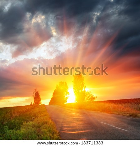 Old road in a field against a dramatic sunset  - stock photo