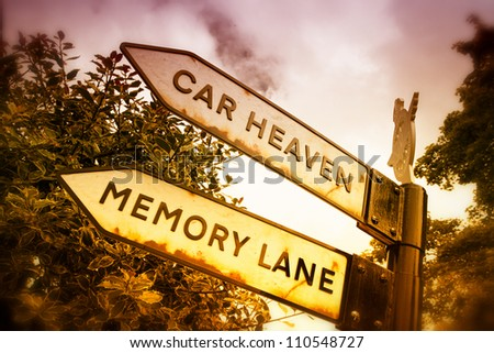 Old road sign showing the way to a automobile breaker. Filters used to reflect the mood. - stock photo