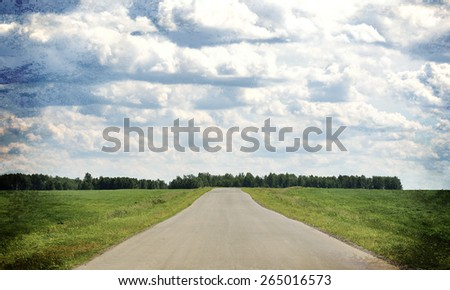 Old road stretches into the distance. On edges of roadsides and green grass field. Sky with clouds in background - stock photo