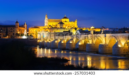 Old roman bridge and  Mosque-cathedral of Cordoba in evening  - stock photo