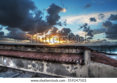 old roof by the sea at sunset in Alghero, Italy - stock photo