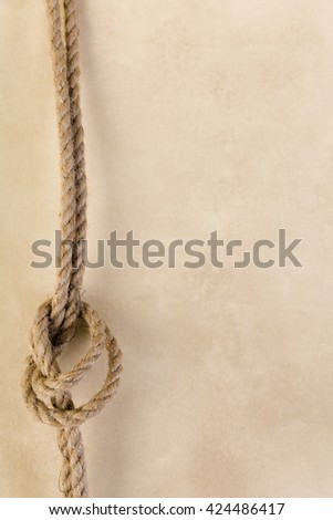 Old rope knot hanging on a vintage wallpaper backdrop - stock photo