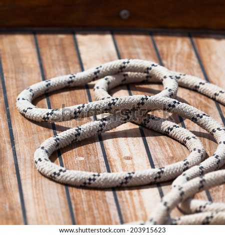 Old rope on a wooden boat deck. Square shot - stock photo