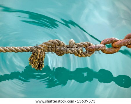 Old rope with older chain above the  water surface, somewhere in Adriatic Sea. - stock photo