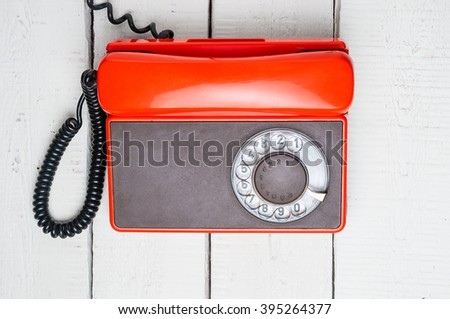 Old rotary telephone on wooden background. Top view - stock photo