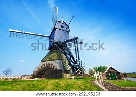 Old rotating water pumping windmill in Holland - stock photo